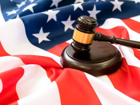 Wooden judge gavel and soundboard laying over USA Flag